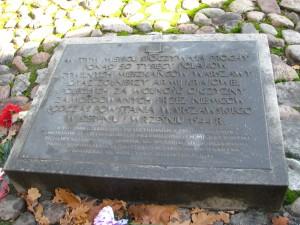 W tym miejscu pod tą tablicą wsypano prochy ponad pięćdziesięciu tysięcy cywilów warszawy zamordowanych w Sierpniu i Wrześniu 1944 r